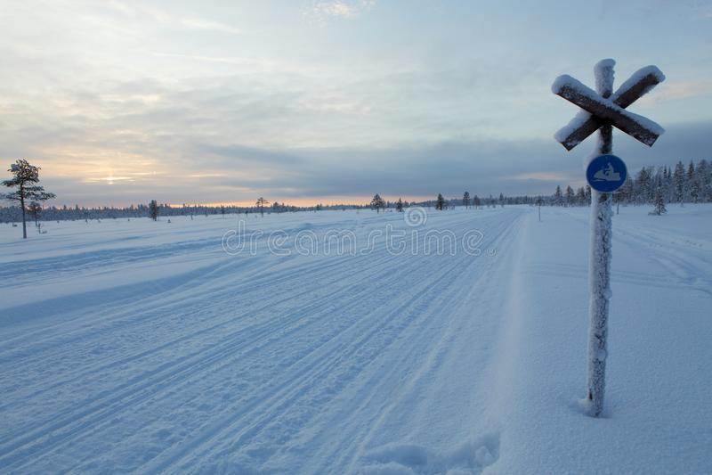 Παγωμένη διαδρομή οχήματος για το χιόνι σε ένα νεφελώδες ηλιοβασίλεμα, Lapland στοκ φωτογραφία με δικαίωμα ελεύθερης χρήσης