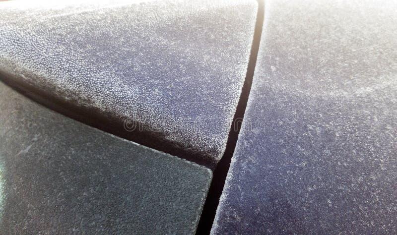 Παγωμένη δροσιά στον οπίσθιο ανεμοφράκτη και το στυλοβάτη γ ενός μπλε αυτοκινήτου hatchback στοκ φωτογραφία με δικαίωμα ελεύθερης χρήσης