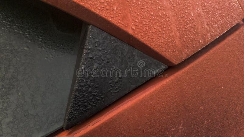Παγωμένη δροσιά στον οπίσθιο ανεμοφράκτη και το στυλοβάτη γ του κόκκινου αυτοκινήτου hatchback στοκ εικόνες