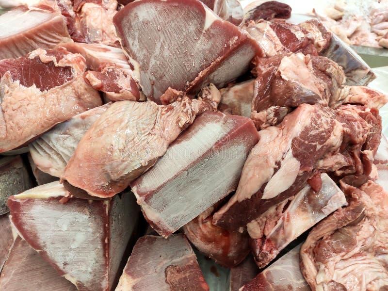 Παγωμένη περικοπή κρέατος στους κύβους και τις φέτες και επιτρεμμένος να λειώσει στον πίνακα στοκ εικόνες