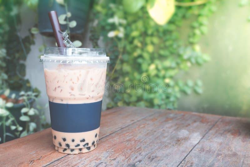 Παγωμένη φυσαλίδα καφέ με το πλαστικό take-$l*away γυαλί στον ξύλινο πίνακα στοκ εικόνες με δικαίωμα ελεύθερης χρήσης