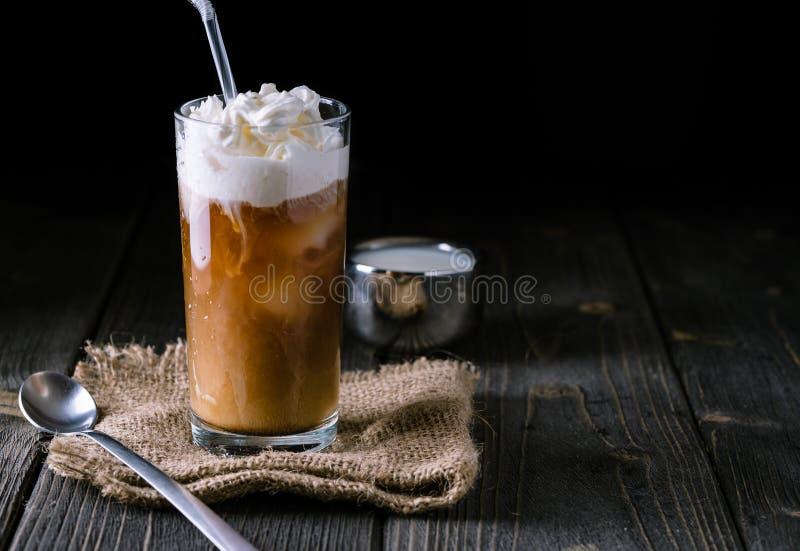 Παγωμένος καφές σε ένα ψηλό γυαλί με την κρέμα που χύνεται στοκ φωτογραφίες