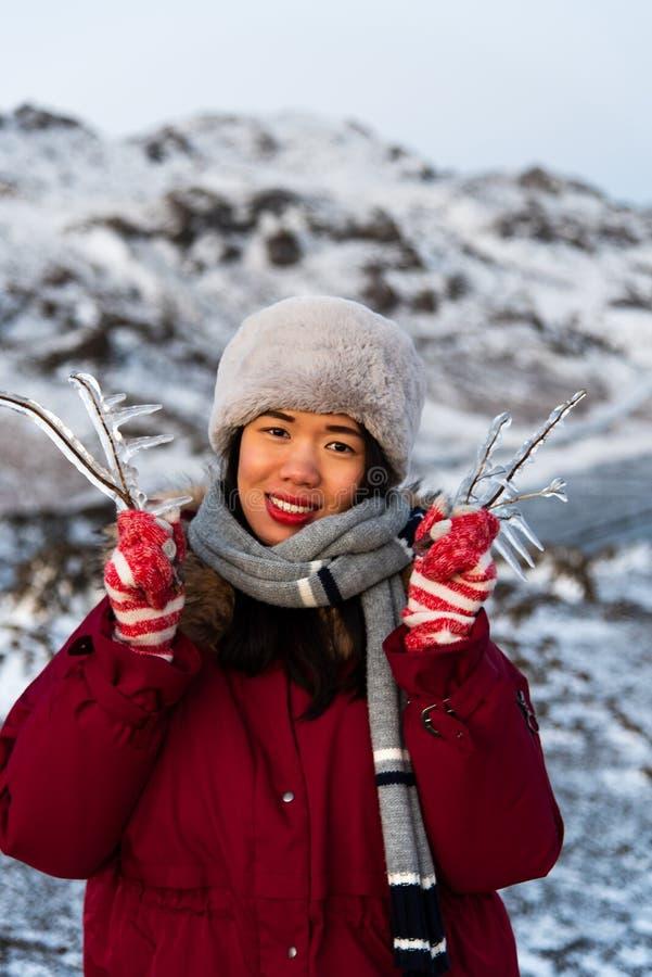 Παγωμένος κλάδος δέντρων κοριτσιών εκμετάλλευση από τη λίμνη στοκ εικόνες