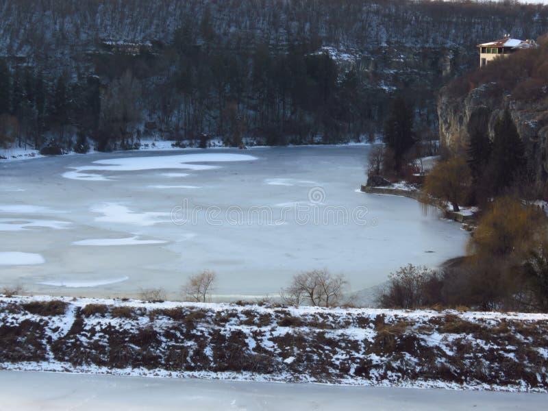 Παγωμένος ποταμός, λίμνη, λίμνη Χειμώνας στα βουνά Ένα μικρό σπίτι στα βουνά το χειμώνα Πρόγνωση καιρού στοκ φωτογραφία