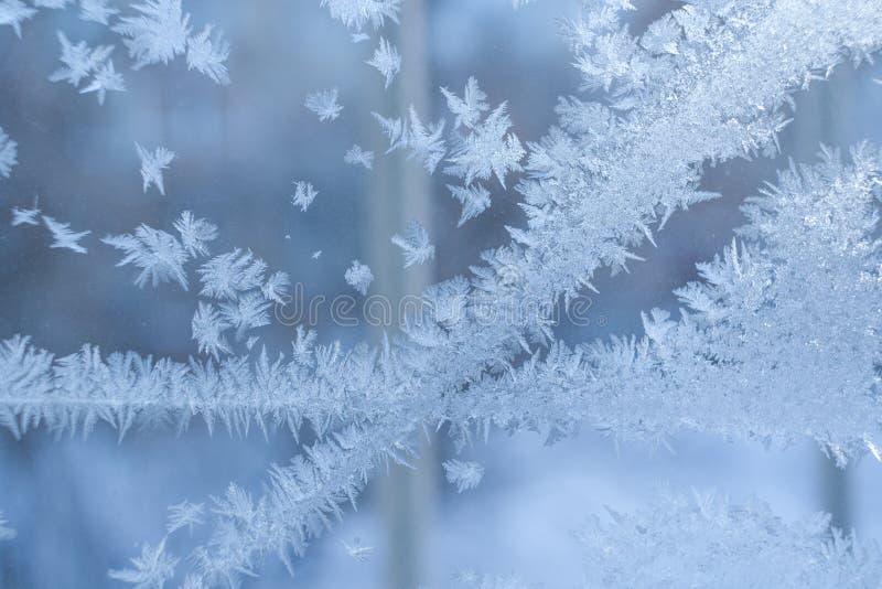 Παγωμένο σχέδιο Tracery δύο τεμνόμενων λωρίδων στο χειμερινό μπλε παράθυρο στοκ εικόνα με δικαίωμα ελεύθερης χρήσης