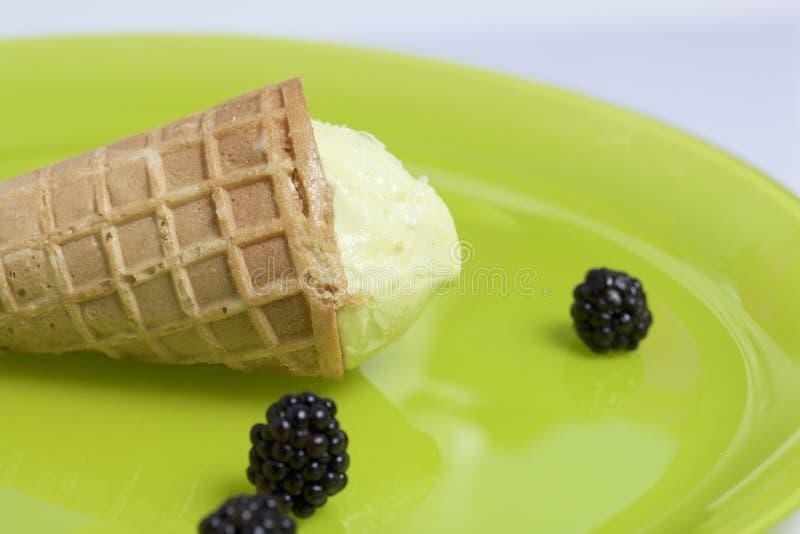Παγωτό σε ένα κέρατο βαφλών Να βρεθεί σε ένα ανοικτό πράσινο πιάτο Κοντινός μερικά μούρα των βατόμουρων στοκ φωτογραφία με δικαίωμα ελεύθερης χρήσης