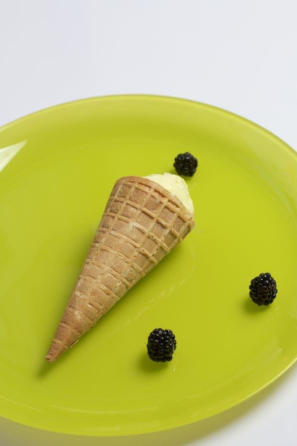 Παγωτό σε ένα κέρατο βαφλών Να βρεθεί σε ένα ανοικτό πράσινο πιάτο Κοντινός μερικά μούρα των βατόμουρων στοκ εικόνες