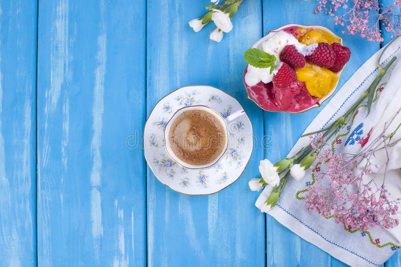 Παγωτό των διαφορετικών χρωμάτων σε ένα μπλε υπόβαθρο Σμέουρα και μάγκο Ντεκόρ των λουλουδιών και του καφέ πρωινού Ελεύθερου χώρο στοκ εικόνες