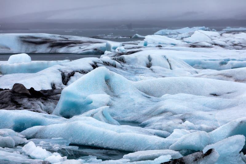 Παγόβουνα που επιπλέουν στη λιμνοθάλασσα Jokulsarlon από τη νότια ακτή ο στοκ φωτογραφία