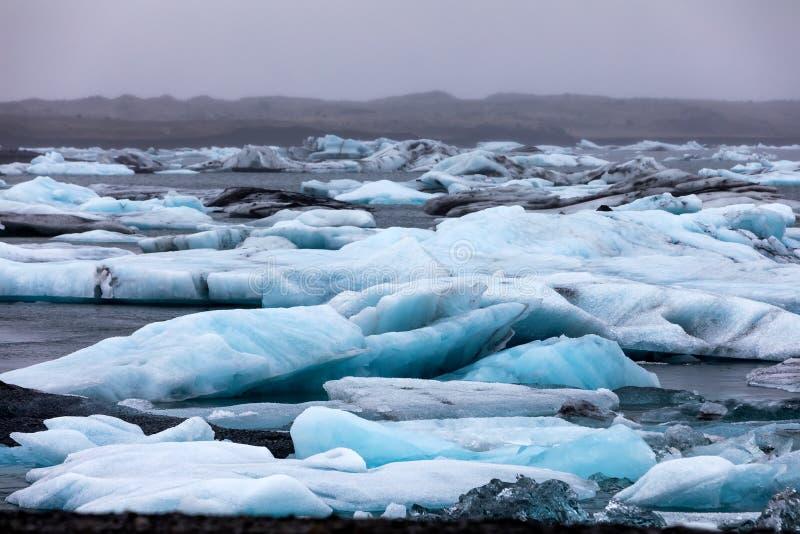 Παγόβουνα που επιπλέουν στη λιμνοθάλασσα Jokulsarlon από τη νότια ακτή ο στοκ φωτογραφία με δικαίωμα ελεύθερης χρήσης