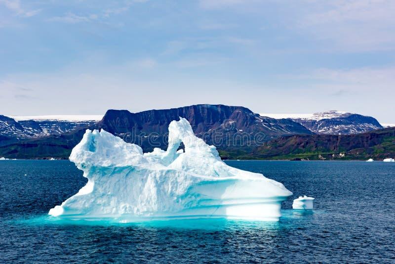 Παγόβουνο που λάμπει στον ήλιο άσπρος και τυρκουάζ πέρα από το σκούρο μπλε αρκτικό ωκεανό, Γροιλανδία στοκ εικόνα με δικαίωμα ελεύθερης χρήσης