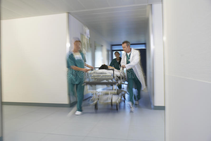 Παθολόγοι που κινούν τον ασθενή σε Gurney μέσω του διαδρόμου νοσοκομείων στοκ φωτογραφίες