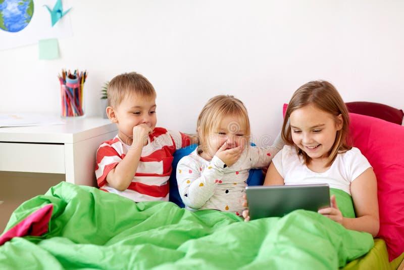 Παιδάκια με το PC ταμπλετών στο κρεβάτι στο σπίτι στοκ φωτογραφία