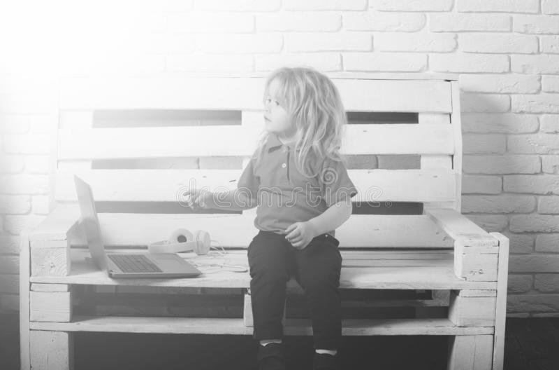 παιδάκι που φορά το ακουστικό κοντά στο lap-top στο άσπρο υπόβαθρο στοκ φωτογραφία