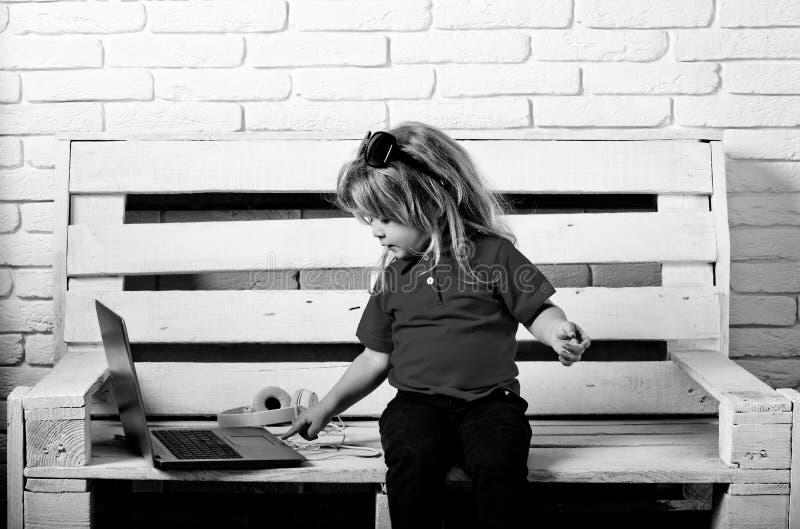 Παιδί ή μικρό αγόρι με το lap-top και τα ακουστικά στοκ εικόνες