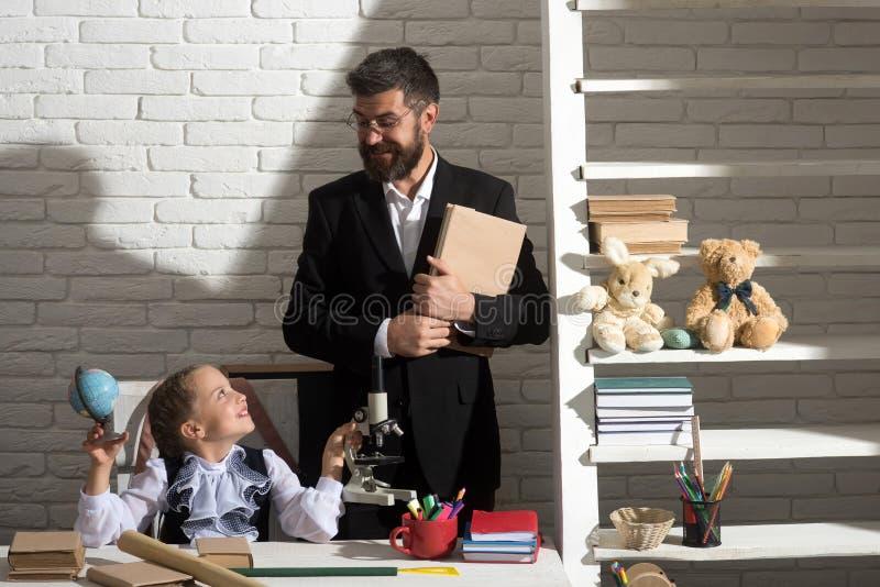 Παιδί και άτομο στο γραφείο με τα σχολικά στοιχεία στοκ εικόνες