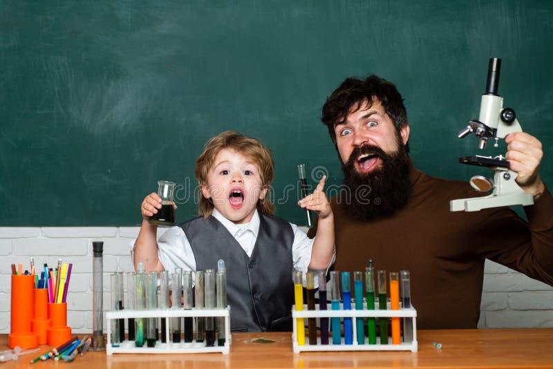 Παιδί και δάσκαλος στο δωμάτιο κατηγορίας Μαθήματα σχολικής χημείας tutoring E r στοκ εικόνες