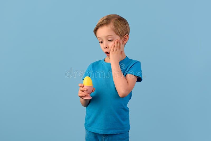 Παιδί και Πάσχα Το χαμογελώντας ξανθό αγόρι, 6 χρονών, κρατά ένα κίτρινο αυγό στο χέρι του στοκ φωτογραφία
