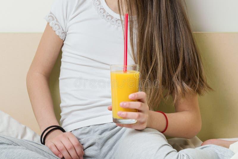 Παιδί κοριτσιών με ένα γυαλί της φρέσκιας συνεδρίασης χυμού από πορτοκάλι στο σπίτι στο κρεβάτι Γυαλί με την κινηματογράφηση σε π στοκ εικόνα