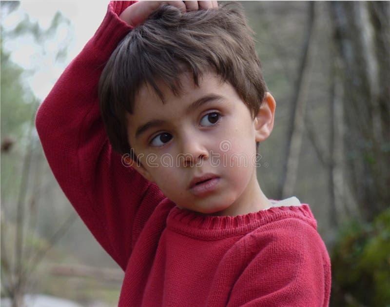 Παιδί με τα μαυρισμένα μάτια και το κόκκινο πουλόβερ στοκ εικόνες με δικαίωμα ελεύθερης χρήσης
