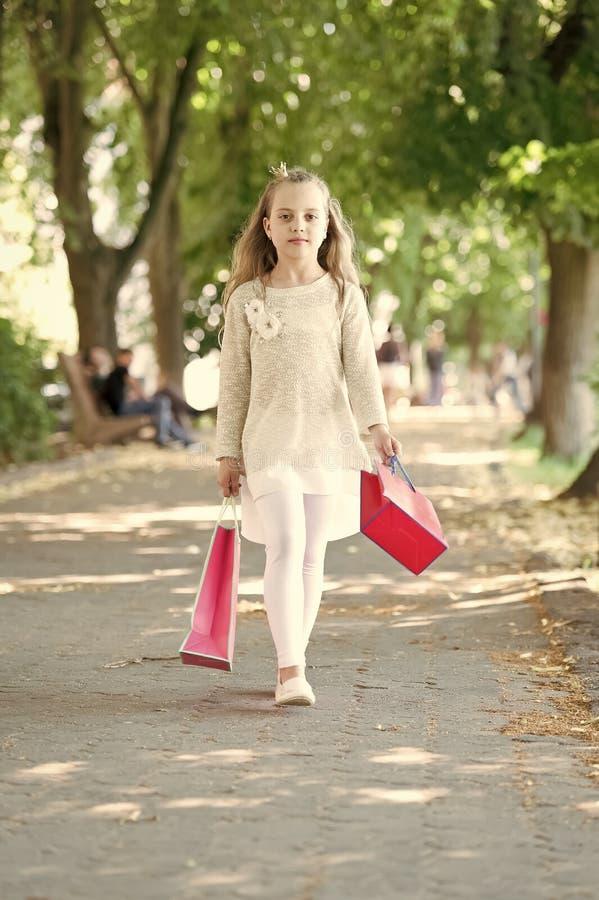 Παιδί με τις τσάντες εγγράφου το καλοκαίρι Κορίτσι με τον περίπατο τσαντών αγορών στο πάρκο Λίγη πριγκήπισσα με την κορώνα στα μα στοκ εικόνες με δικαίωμα ελεύθερης χρήσης
