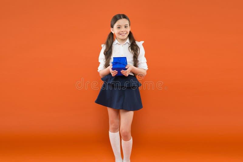 Παιδί με το παρόν κιβώτιο επόμενη μέρα των Χριστουγέννων αγορές σχολικής αγοράς έξυπνο και ευφυές παιδί στον πορτοκαλή τοίχο o στοκ φωτογραφίες
