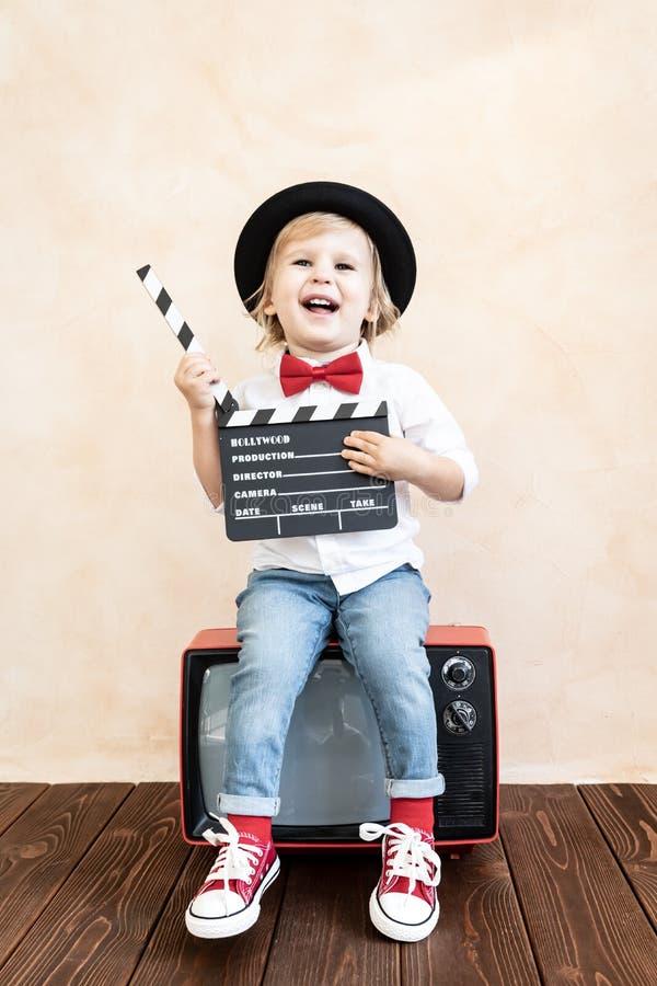 Παιδί με clapper τον πίνακα που παίζει στο σπίτι στοκ φωτογραφία με δικαίωμα ελεύθερης χρήσης