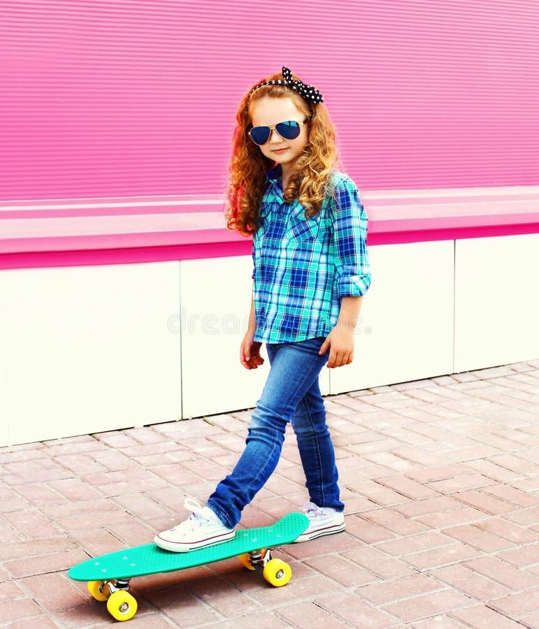 Παιδί μικρών κοριτσιών μόδας στο ελεγμένο πουκάμισο με skateboard στην πόλη στο ζωηρόχρωμο ροζ στοκ φωτογραφίες με δικαίωμα ελεύθερης χρήσης