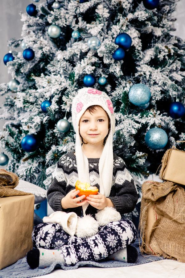 Παιδί μικρών κοριτσιών πέντε ετών που κάθεται στο πάτωμα κοντά στο χριστουγεννιάτικο δέντρο που διακοσμείται με τα παιχνίδια, σφα στοκ εικόνα
