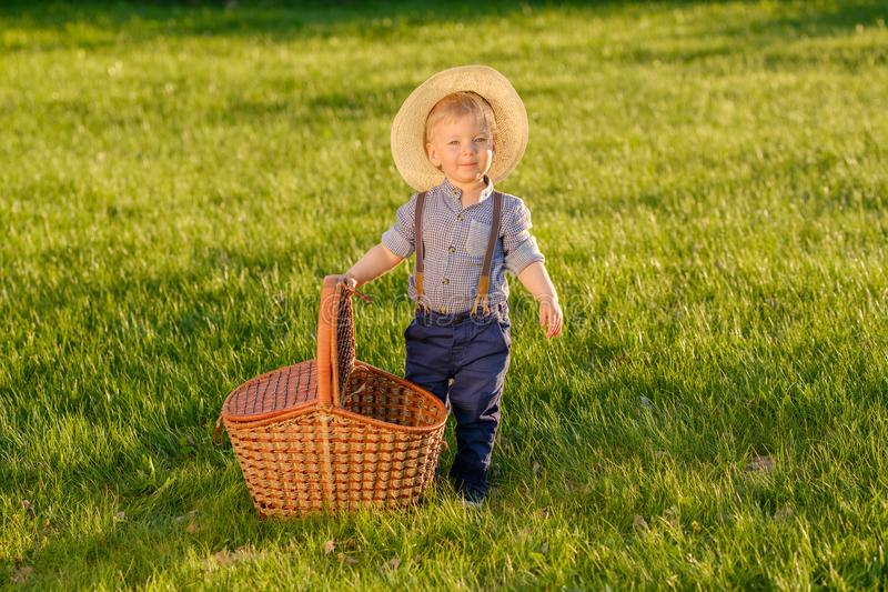 Παιδί μικρών παιδιών υπαίθρια Αγοράκι ενός έτους βρεφών που φορά το καπέλο αχύρου με το καλάθι πικ-νίκ στοκ φωτογραφία με δικαίωμα ελεύθερης χρήσης