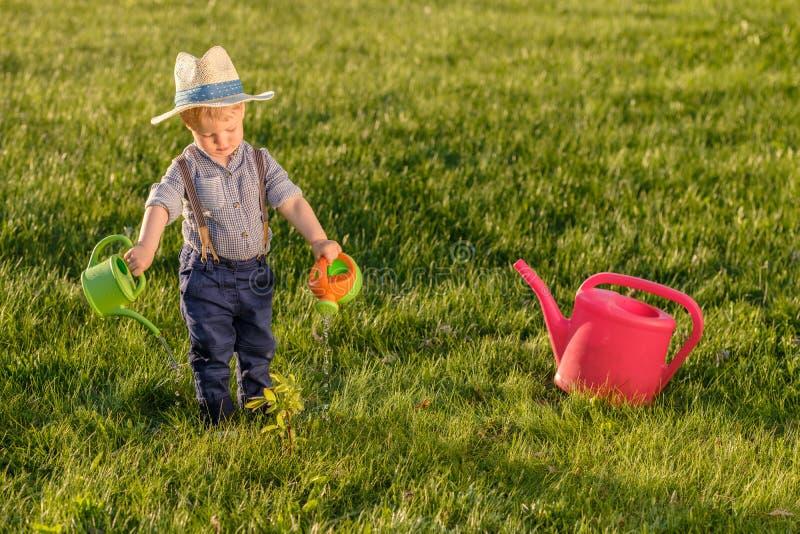 Παιδί μικρών παιδιών υπαίθρια Το αγοράκι ενός έτους βρεφών που φορά το καπέλο αχύρου που χρησιμοποιεί το πότισμα μπορεί στοκ φωτογραφία