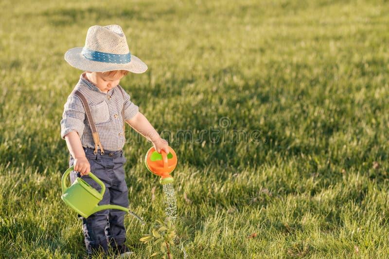 Παιδί μικρών παιδιών υπαίθρια Το αγοράκι ενός έτους βρεφών που φορά το καπέλο αχύρου που χρησιμοποιεί το πότισμα μπορεί στοκ εικόνα