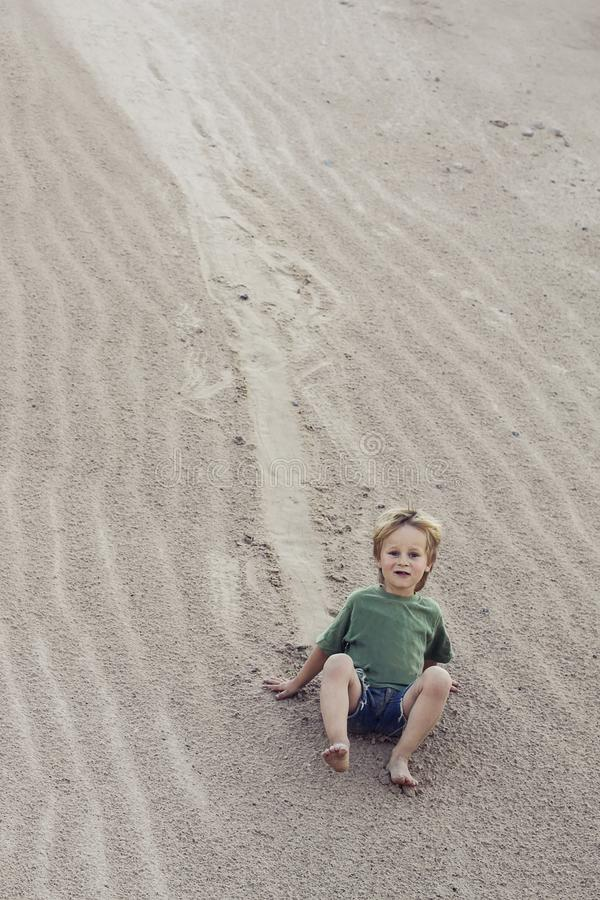 Παιδί που έρχεται κάτω στην άμμο στο βουνό άμμου στοκ εικόνες με δικαίωμα ελεύθερης χρήσης