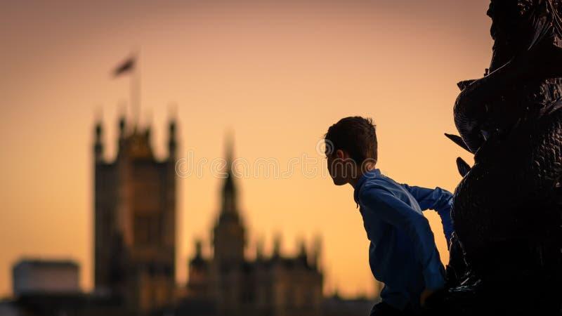 Παιδί που αναρριχείται σε μια θέση λαμπτήρων στο South Bank στο Λονδίνο UK στο ηλιοβασίλεμα με τις Βουλές του Κοινοβουλίου στο υπ στοκ εικόνες με δικαίωμα ελεύθερης χρήσης