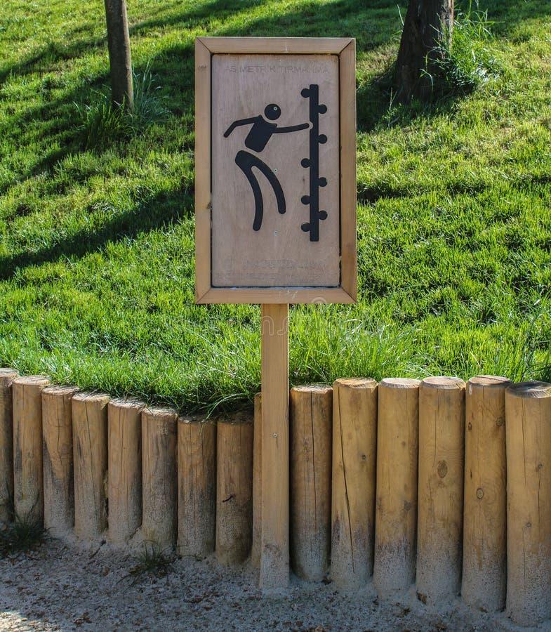 Παιδί που αναρριχείται στο προειδοποιητικό σημάδι στο πάρκο στοκ εικόνες