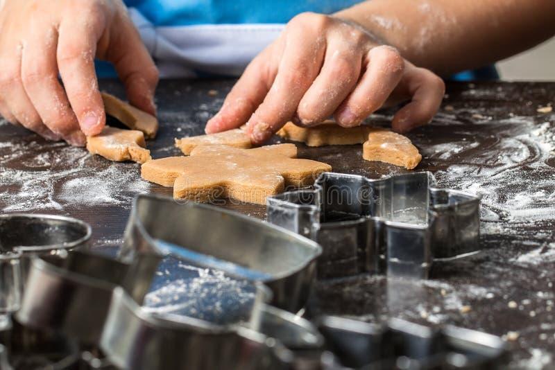 Παιδί που αποκόπτει τα μπισκότα από την κουζίνα ζύμης στο σπίτι στοκ εικόνα