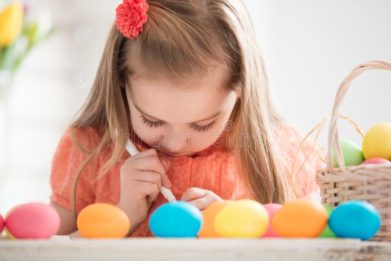 Παιδί που δημιουργεί τα σχέδια στα ζωηρόχρωμα βαμμένα αυγά στοκ εικόνες