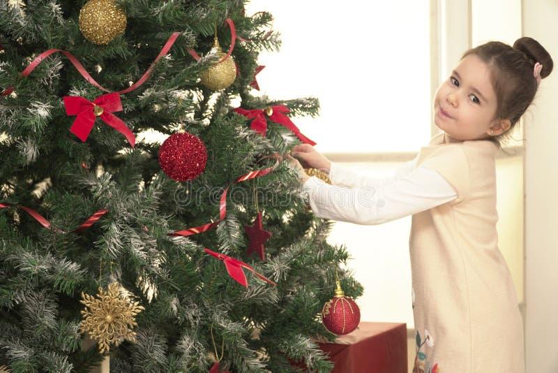Παιδί που διακοσμεί το χριστουγεννιάτικο δέντρο στο οικογενειακό καθιστικό στοκ εικόνες