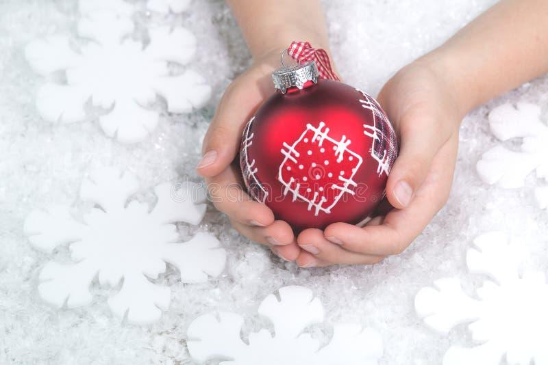 Παιδί που κρατά το κόκκινο μπιχλιμπίδι Χριστουγέννων προσθηκών στο λευκό στοκ φωτογραφία