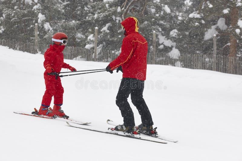 Παιδί που μαθαίνει πώς να κάνει σκι με τον εκπαιδευτικό Χειμερινός αθλητισμός στοκ φωτογραφία με δικαίωμα ελεύθερης χρήσης