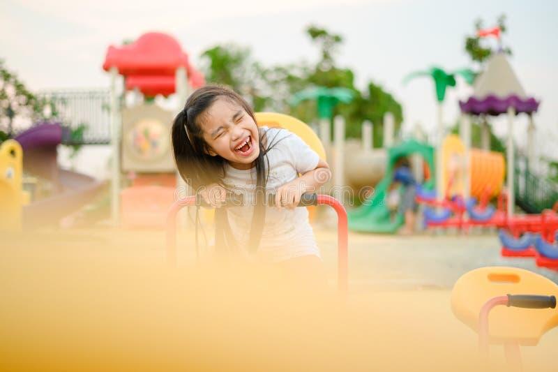 Παιδί που παίζει έχοντας τη διασκέδαση στην παιδική χαρά στοκ φωτογραφία