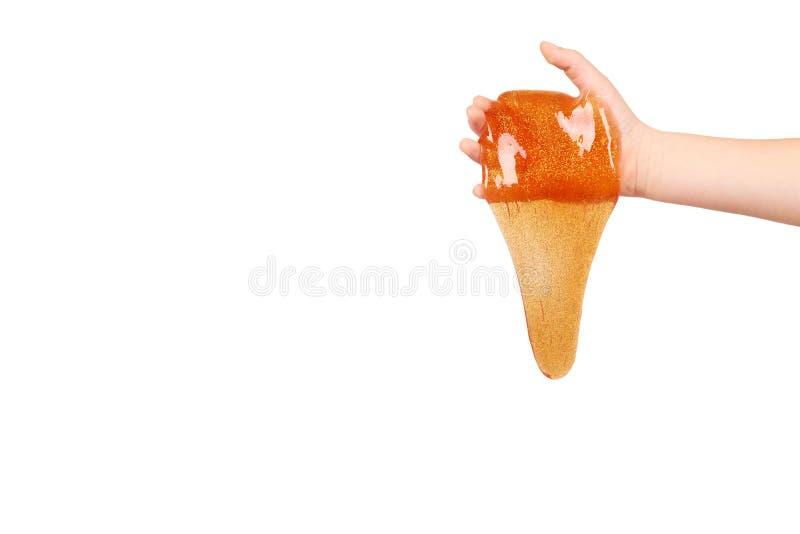 παιδί που παίζει πορτοκαλί slime με το χέρι, διαφανές παιχνίδι στοκ φωτογραφία