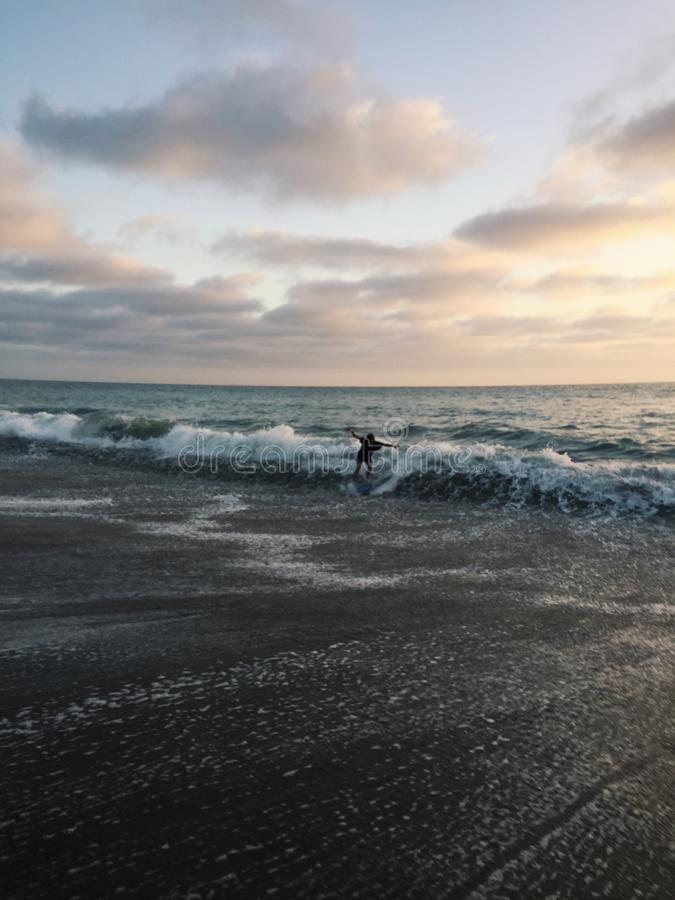 Παιδί που παίρνει χτυπημένο από το κύμα στην παραλία στοκ φωτογραφία