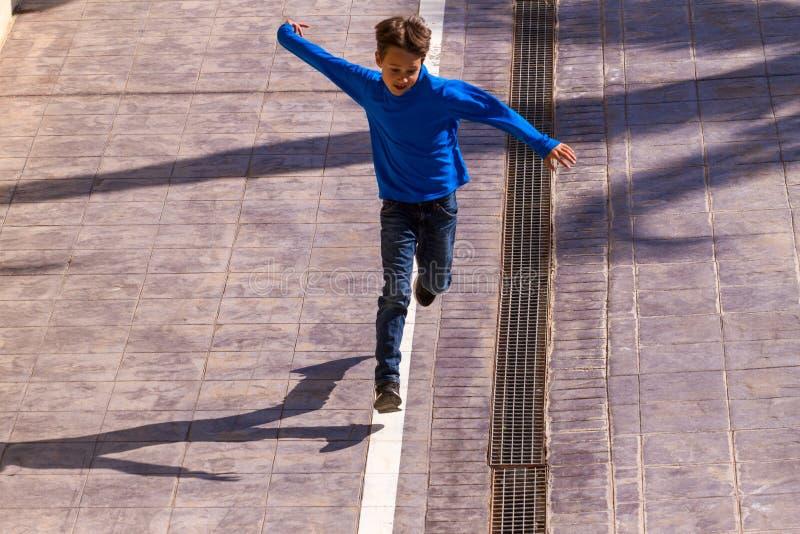Παιδί που πηδά, τρέξιμο υπαίθριο στην ηλιόλουστη ημέρα στοκ φωτογραφία