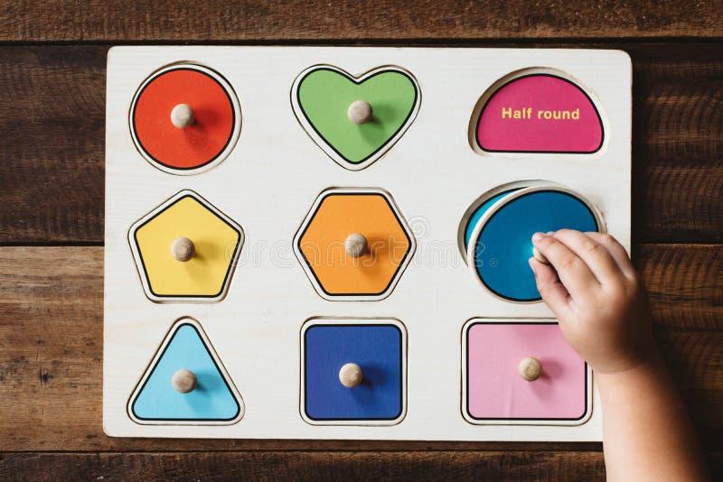 Παιδί που ταιριάζει με έναν γρίφο μορφής παιχνιδιών στον ξύλινο πίνακα στοκ εικόνα με δικαίωμα ελεύθερης χρήσης