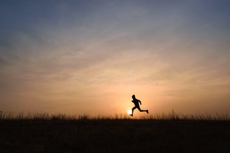 Παιδί που τρέχει πέρα από τον ορίζοντα στην ανατολή στοκ εικόνα