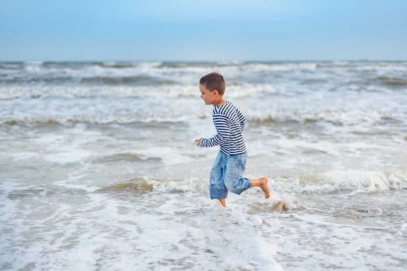 Παιδί που τρέχει στην παραλία r ευτυχές παιχνίδι παιδιών στην παραλία στο χρόνο ηλιοβασιλέματος στοκ φωτογραφίες
