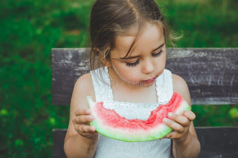 παιδί που τρώει το καρπούζι στον κήπο Τα παιδιά τρώνε τα φρούτα υπαίθρια Υγιές πρόχειρο φαγητό για τα παιδιά Όμορφο υπόβαθρο, κορ στοκ εικόνες