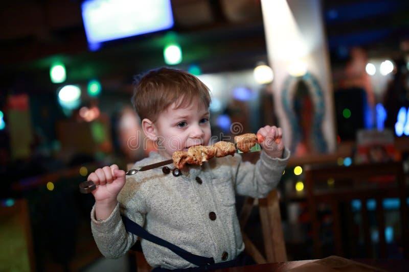 Παιδί που τρώει kebab στο οβελίδιο στοκ εικόνα με δικαίωμα ελεύθερης χρήσης