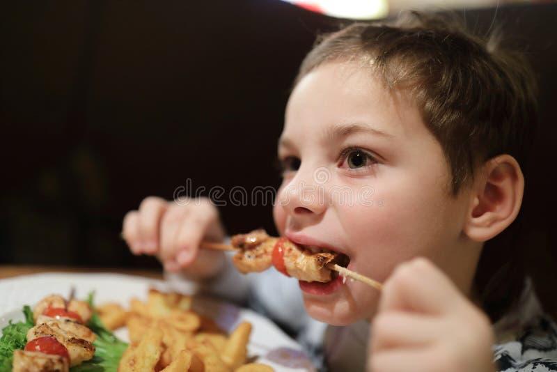 Παιδί που τρώει kebab στο οβελίδιο στοκ φωτογραφία